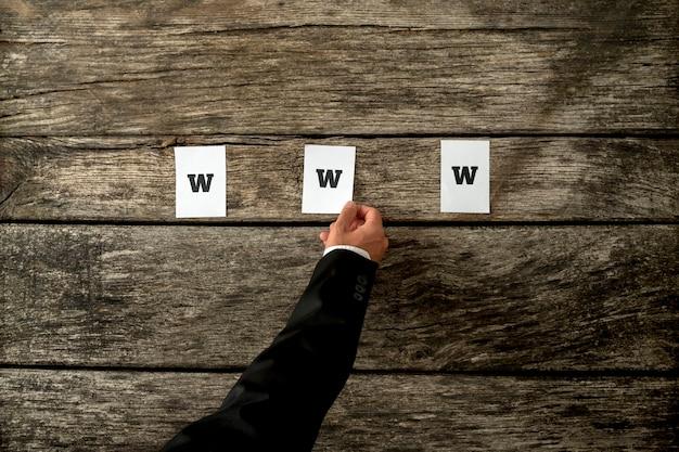 Vista de alto ângulo do desenvolvedor da web, colocando três white papers soletrando www em pranchas de madeira rústicas texturizadas. conceitual de profissionais da web da internet.