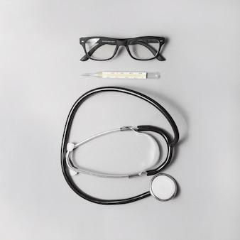 Vista de alto ângulo do estetoscópio; termômetro e óculos no fundo cinza