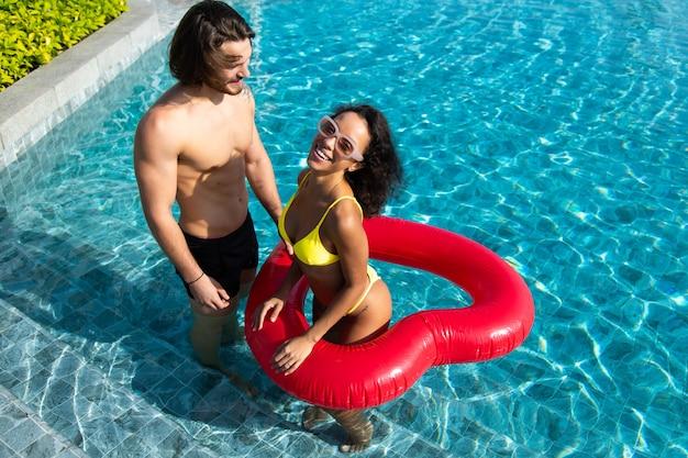 Vista de alto ângulo do jovem casal feliz à beira da piscina. casal está relaxando na festa na piscina. conceito de férias de verão