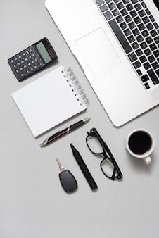 Vista de alto ângulo do laptop; calculadora; bloco de notas em branco; óculos; e xícara de café com chave no pano de fundo cinzento