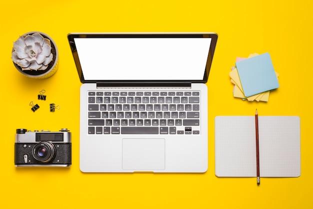 Vista de alto ângulo do laptop; câmera; artigos de papelaria e planta suculenta na superfície amarela