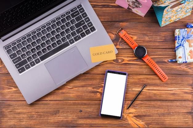 Vista de alto ângulo do laptop; celular; presente; e cartão de ouro na mesa de madeira