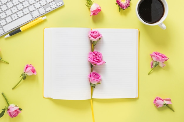 Vista de alto ângulo do notebook; caneta; flores; teclado e chá preto em pano de fundo amarelo