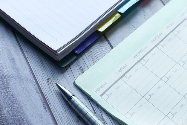 Vista de alto ângulo do planejador semanal e do bloco de notas na mesa.