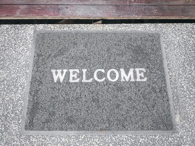 Vista de alto ângulo do tapete cinza com etiqueta de texto de boas-vindas branca