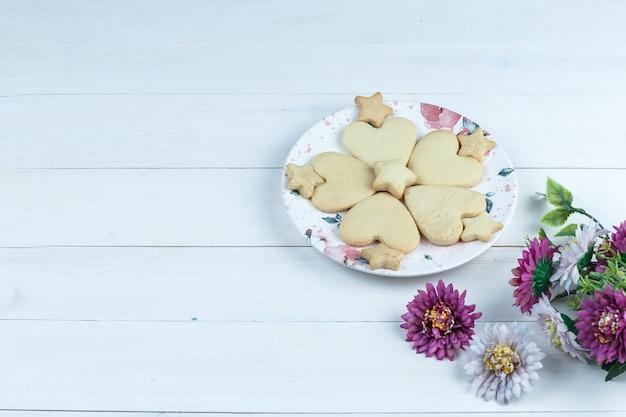 Vista de alto ângulo em forma de coração e biscoitos estrela em prato branco com flores