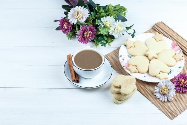 Vista de alto ângulo em formato de coração e biscoitos em forma de estrela, flores em uma mesa redonda com uma xícara de café