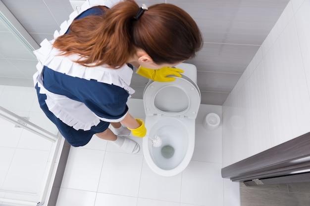 Vista de alto ângulo em uma empregada doméstica de avental branco, vestido azul e chinelos brancos, limpando a bacia do vaso sanitário branco aberto no banheiro