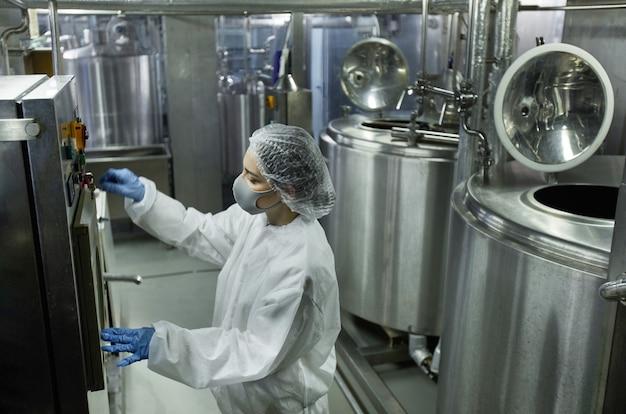 Vista de alto ângulo em unidades de máquina operando jovem trabalhadora enquanto trabalhava em uma fábrica de alimentos limpos, copie o espaço