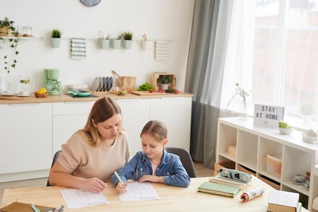 Vista de alto ângulo na mãe carinhosa, ajudando a linda garota fazendo a lição de casa e estudando em casa em um interior aconchegante.