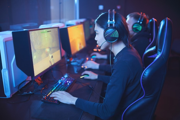 Vista de alto ângulo para jovem asiático jogando videogame com a equipe de ciberesporte profissional.