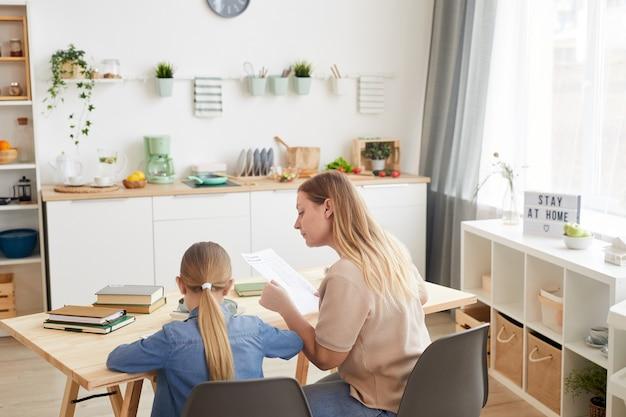 Vista de alto ângulo para mãe adulta ajudando filha enquanto estudava em casa juntos, copie o espaço