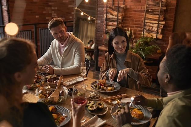 Vista de alto ângulo para um grupo de pessoas adultas alegres, sentadas à mesa de jantar, enquanto aproveitam a festa com iluminação externa