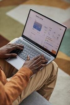 Vista de alto ângulo para um homem afro-americano usando um laptop com o serviço bancário na tela, copie o espaço