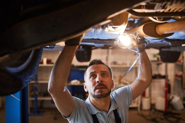 Vista de alto ângulo para um mecânico maduro olhando embaixo do carro no elevador e segurando a luz da lâmpada durante a inspeção na oficina de conserto de automóveis, copie o espaço