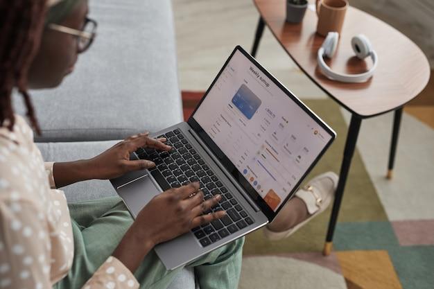 Vista de alto ângulo para uma jovem afro-americana usando um laptop com serviço bancário na tela, copie o espaço