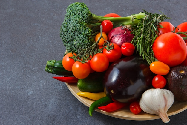 Vista de alto ângulo, um monte de tomate com pimenta, cebola, berinjela, verduras, brócolis, alho na superfície cinza. horizontal