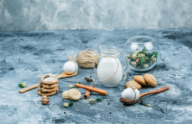 Vista de alto ângulo uma jarra de leite e uma tigela de vidro de iogurte com colheres, biscoitos, ovos, clew, canela e uma planta em fundo de mármore azul e cinza escuro. espaço livre horizontal para o seu texto