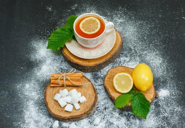 Vista de alto ângulo, uma xícara de chá com limão, canela seca, cubos de açúcar, folhas em fatias de madeira e escuro. horizontal