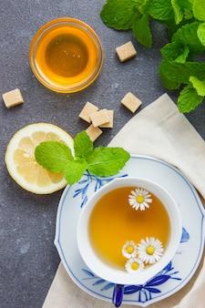 Vista de alto ângulo, uma xícara de chá de camomila com açúcar, folhas, mel, limão
