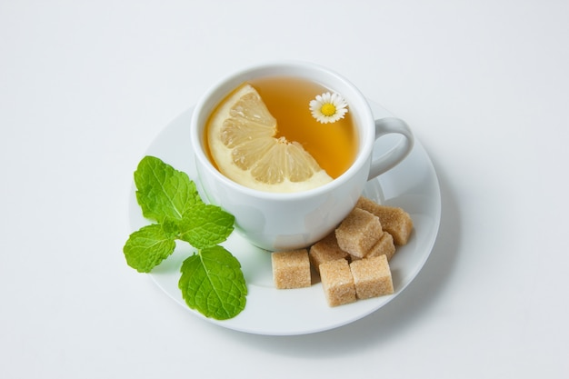 Vista de alto ângulo, uma xícara de chá de camomila com limão, folhas de hortelã, açúcar na superfície branca. horizontal