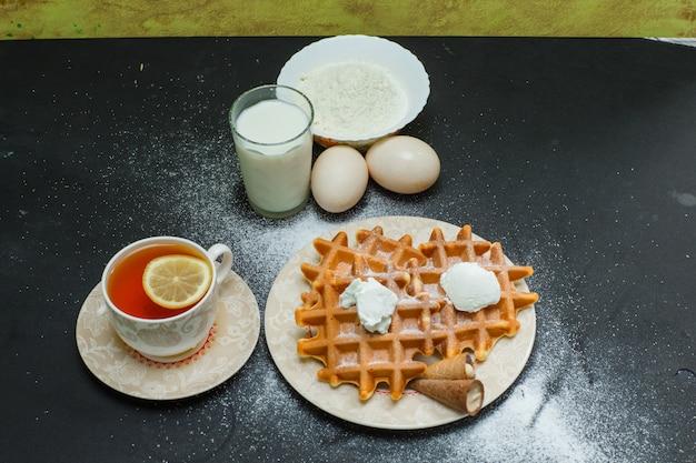 Vista de alto ângulo waffles no prato com chá, ovos, farinha, leite no escuro. horizontal