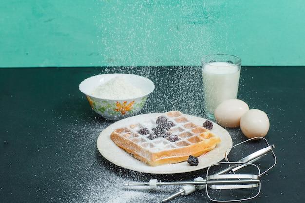 Vista de alto ângulo waffles no prato com ovos, farinha, leite, batedeira varas no escuro e ciano. horizontal