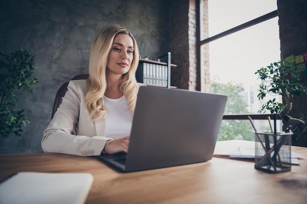 Vista de ângulo baixo, alegre, linda loira empreendedora sentada na mesa com laptop e bloco de notas