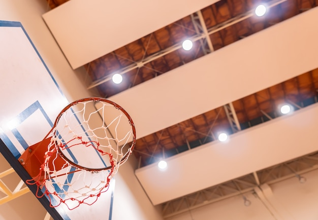 Vista de ângulo baixo da cesta de basquete no ginásio com holofotes de teto,