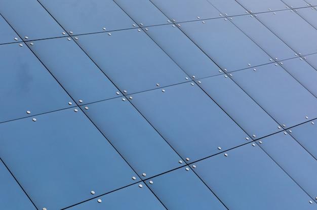 Vista de ângulo baixo da reflexão de vidro azul na construção de fachada