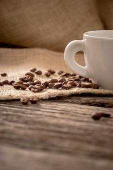 Vista de ângulo baixo de grãos de café espalhados em pano de linho, deitado na mesa de madeira texturizada