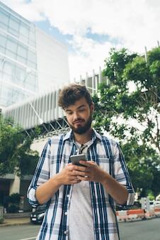 Vista de ângulo baixo de mensagens de texto de cara hipster em smartphone no meio da rua