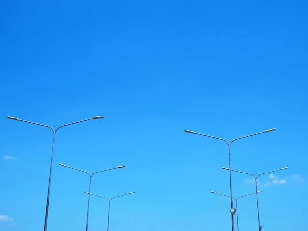 Vista de ângulo baixo de postes de lâmpada contra o céu azul no tempo do dia