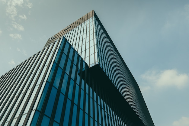 Vista de ângulo baixo de um edifício em uma fachada de vidro sob o lindo céu nublado