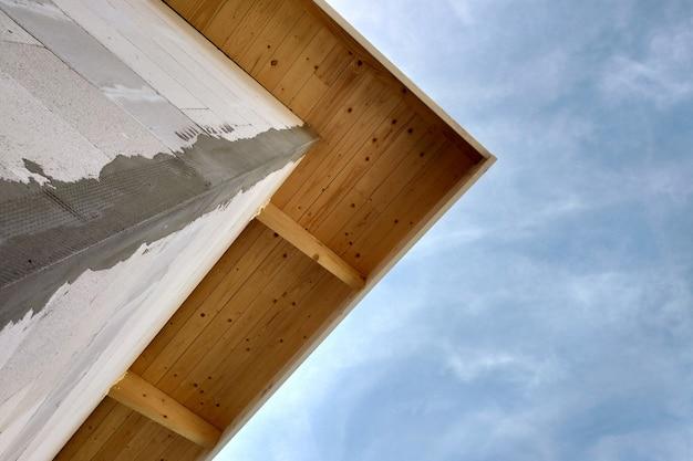 Vista de ângulo baixo de um edifício fasade em parede inacabada de construção e placas de telhado de madeira.