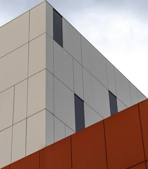 Vista de ângulo baixo de um moderno edifício branco e laranja sob o céu brilhante