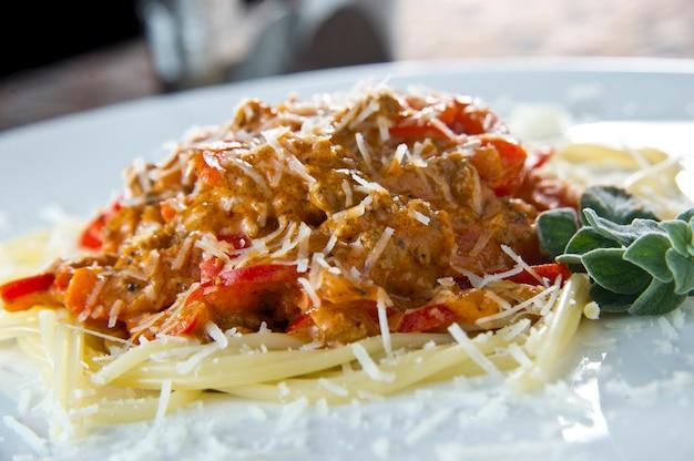 Vista de ângulo baixo de uma porção de espaguete italiano com molho à bolonhesa ou à bolonhesa à base de carne em um prato branco liso