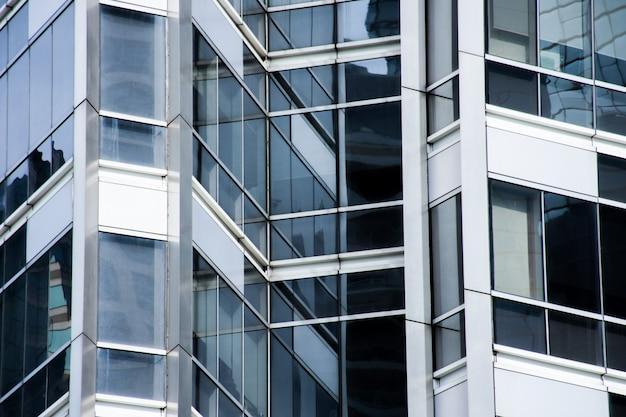Vista de ângulo de perspectiva e de baixo do edifício de vidro moderno com reflexões