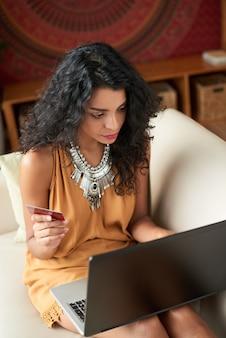 Vista de ângulo superior da jovem mulher inserindo seus dados de cartão para compras on-line