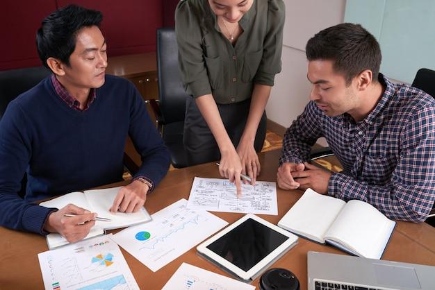 Vista de ângulo superior da mulher compartilhando roteiro com colegas de trabalho