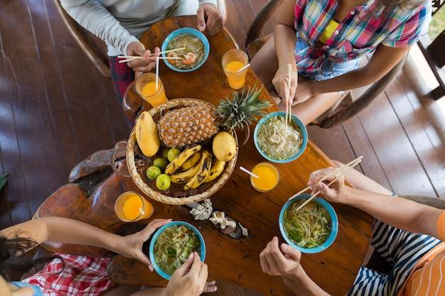 Vista de ângulo superior de pessoas comendo macarrão asiático sopa comida tradicional