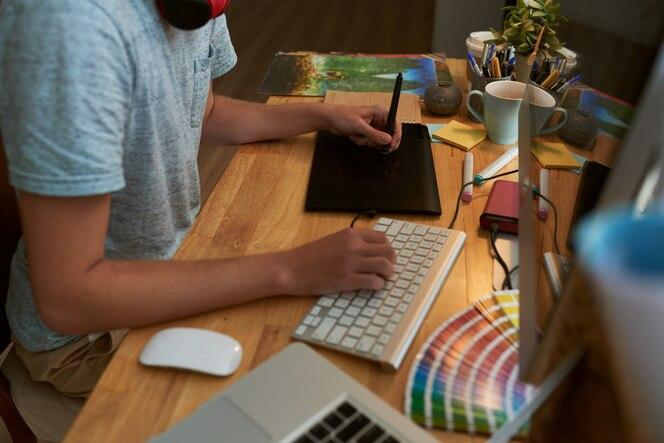 Vista de ângulo superior do web designer masculino no trabalho