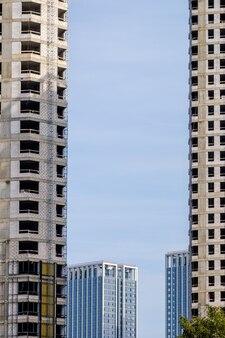Vista de arranha-céus modernos feitos de vidro e concreto contra o céu entre dois prédios inacabados enquadramento urbano natural conceito de construção urbana