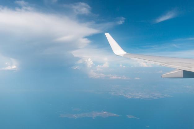Vista de asa de avião pela janela o fundo do céu nublado, viagens e férias conceito de férias