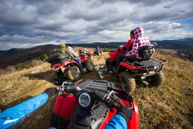 Vista, de, atv, um, grupo pessoas, montando, um, quad, bicicletas, ligado, um, estrada montanha, sob, um, céu, com, nuvens, em, outono