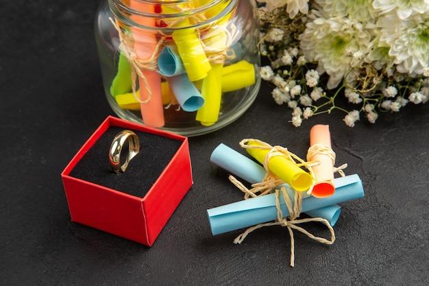 Vista de baixo anel de noivado em caixa de buquê de flores pergaminho papéis de desejo em pote, quer casar comigo escrito em papel na mesa preta