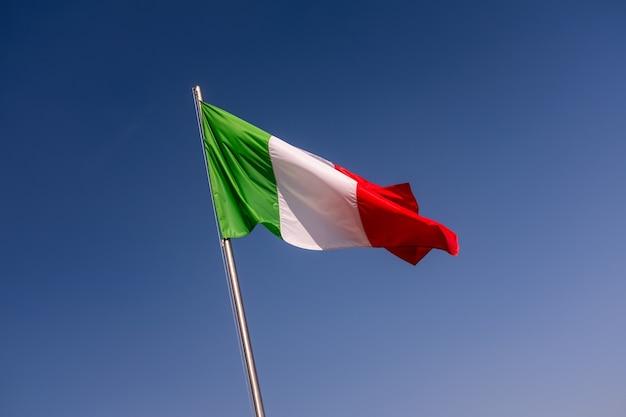 Vista de baixo ângulo da bandeira da itália tremulando no céu azul claro
