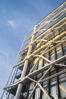 Vista de baixo ângulo da construção de um edifício moderno sob um céu azul e luz do sol