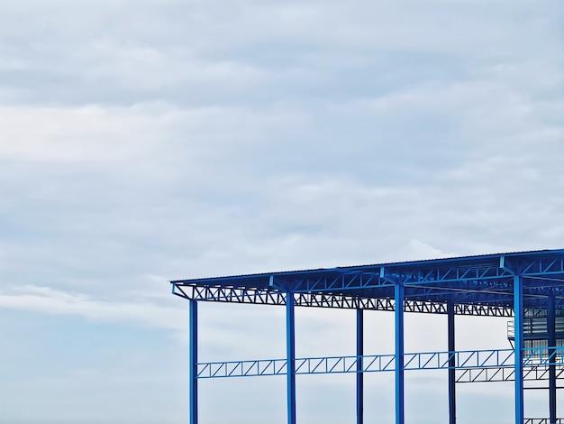 Vista de baixo ângulo da estrutura do armazém azul contra o céu nublado