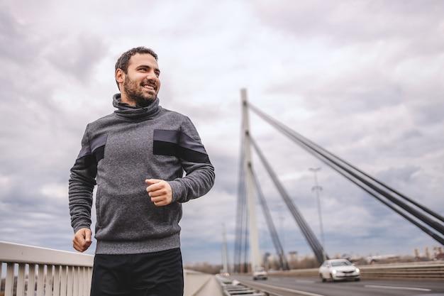 Vista de baixo ângulo de bonito positivo apto desportista em roupas esportivas correndo na ponte em tempo nublado.